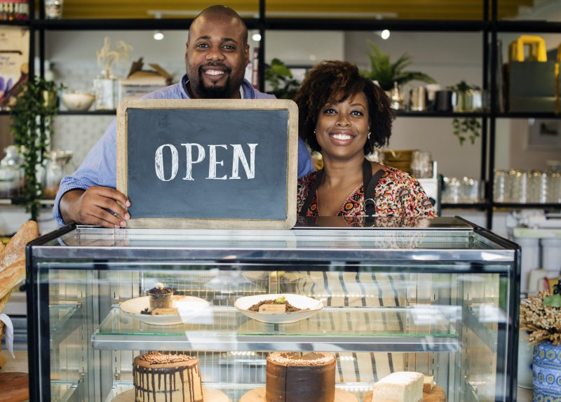 "a couple standing behind a bakery counter holding a sign that reads ""OPEN"""