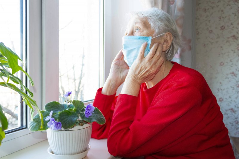 an elderly woman wearing a red sweater and staring out the window with her mask on