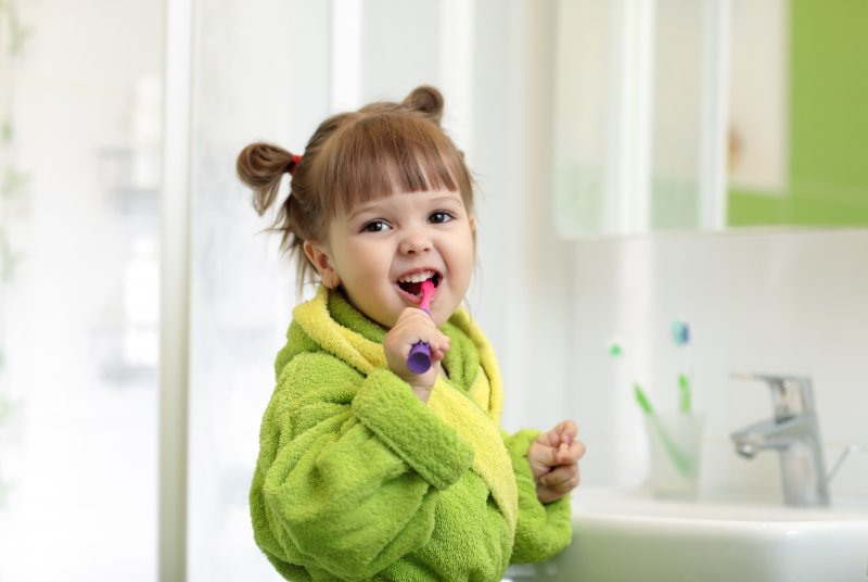 a little girl wearing a green robe and brushing her teeth in the bathroom
