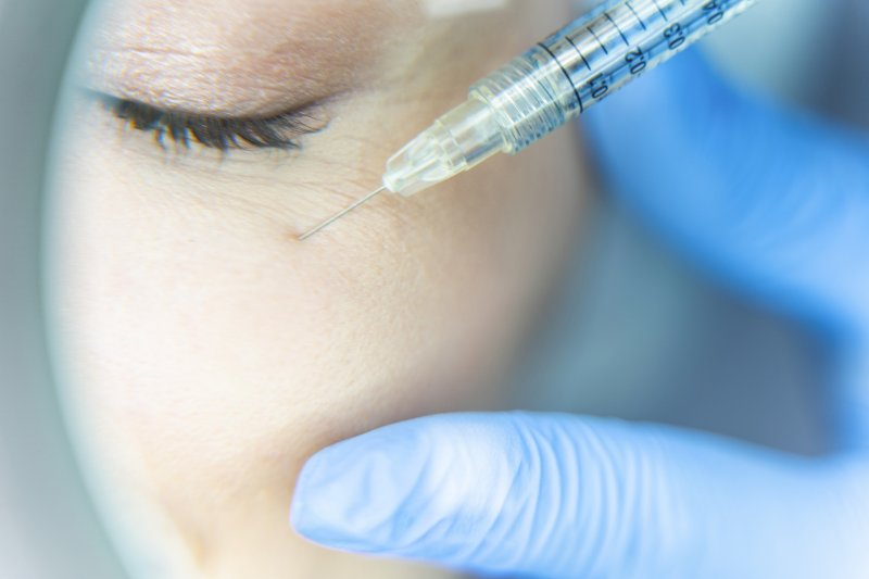 a person receiving a dermal filler injection near their eye