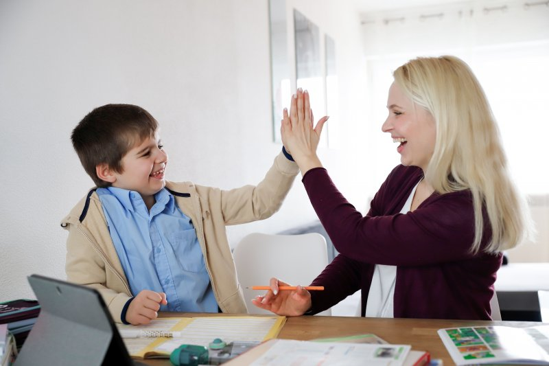 a mother and son high-five while completing schoolwork at home